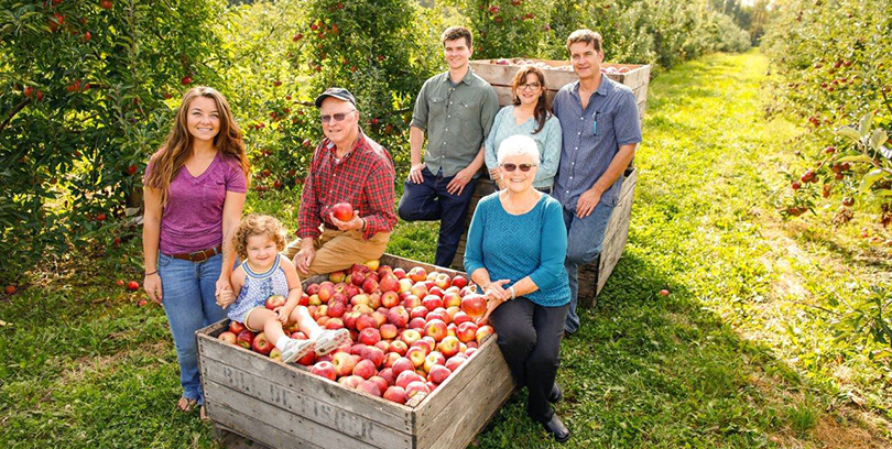 The DeFisher family posing for a group photo with a bushel of apples in the orchard